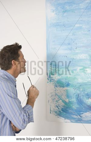 Side view of man observing painting in art gallery