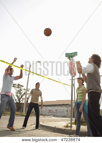 Portrait of smiling young friends playing volleyball over police tape in street