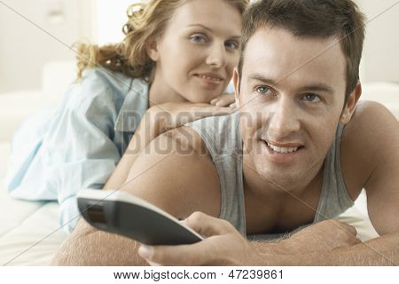 Portrait of young woman with man holding remote control in bed