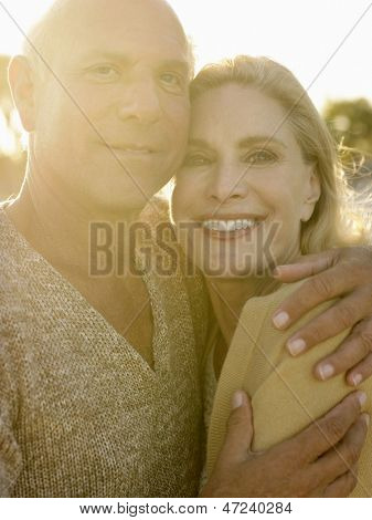 Portrait of senior man embracing woman at sunset on beach