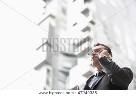 Low angle view of businessman communicating on mobile phone against tall building