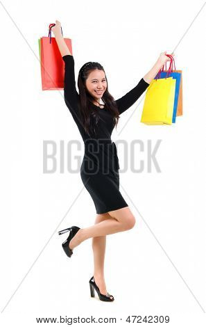 Excited Asian shopping woman happy smiling holding many shopping bags. Asian shopper girl isolated on white background in full length. Beautiful mixed race Caucasian Southeast Asian woman model.