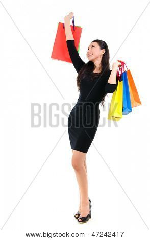 Asian shopping woman happy smiling holding many shopping bags. Asian shopper girl isolated on white background in full length. Beautiful mixed race Caucasian Southeast Asian woman model.