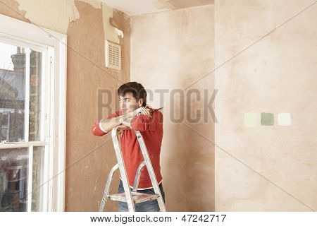 Man looking through window while resting on step ladder in unrenovated room