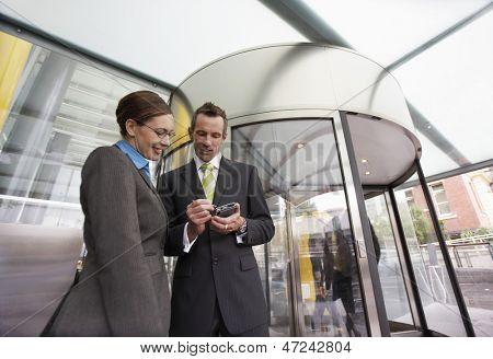 Businessman and businesswoman using PDA in front of revolving door
