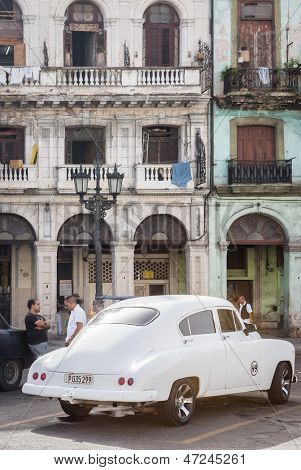 HAVANA-JUNE 21:Old american car next to crumbling buildings on June 21, 2013 in Havana. Before a new law issued on October 2011, cubans could only trade cars that were on the road before 1959