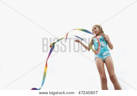Low angle view of young girl playing with stick streamer against sky