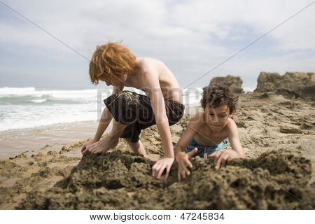 Young preadolescent boys playing in sand at beach