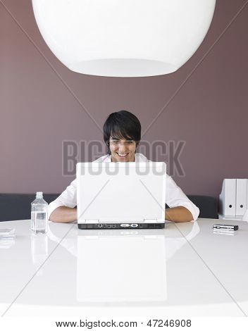 Smiling young businessman using laptop at desk in office