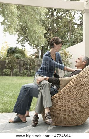 Full length of woman sitting on man's lap in lawn