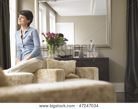 Thoughtful woman looking away while sitting on armrest of armchair