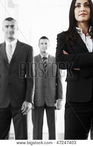 Confident businesswoman with male colleagues in office