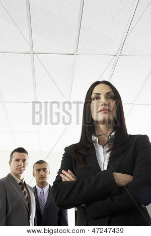 Confident businesswoman with male colleagues in background at office