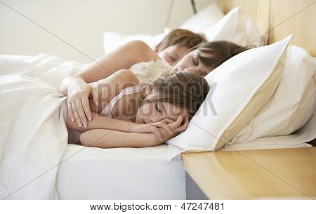 Mother with two children sleeping in bed