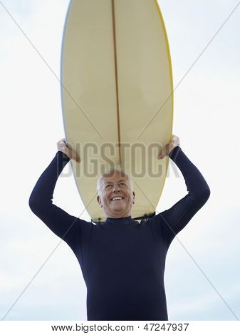 Low angle view of smiling senior man carrying surfboard over head against sky