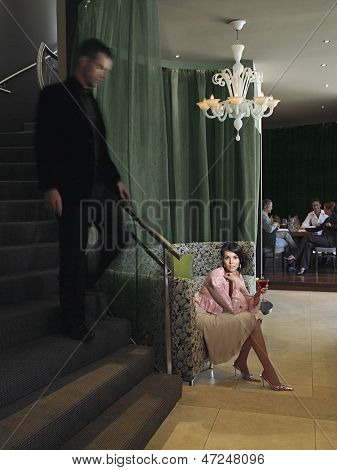 Full length of beautiful young woman waiting in hotel lobby with man descending staircase