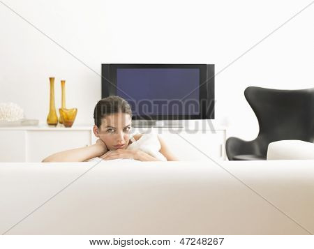 Portrait of beautiful young woman sitting on sofa in modern living room