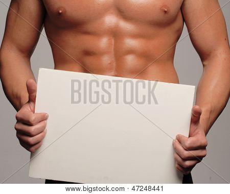 Shaped and healthy body man holding a white panel,,shaped abdominal,
