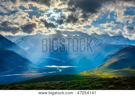 HImalayan valley landscape with Himalayas mountains. Sun rays come through clouds. Himachal Pradesh, India