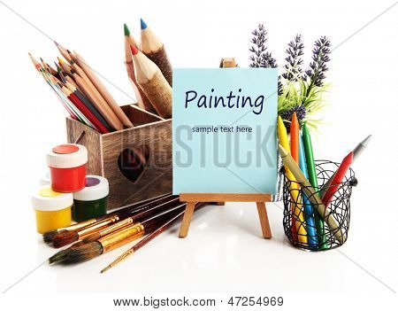 Pencils in wooden crate, paints, brushes and easel, isolated on white