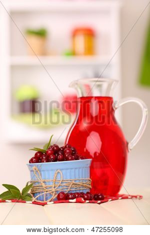 Pitcher of cranberry juice and red cranberries on table