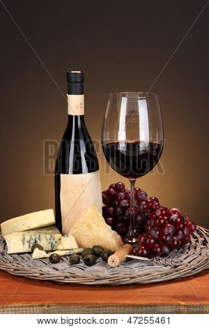 Refined still life of wine, cheese and grapes on wicker tray on wooden table on brown background