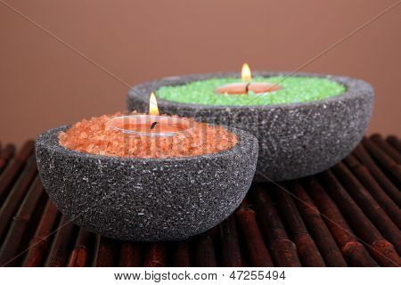 Candles in stone bowls with marine salt, on bamboo mat, on brown background