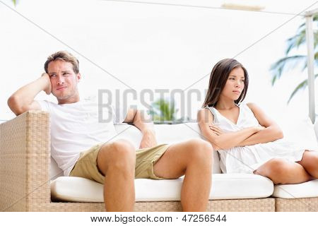 Unhappy couple upset with marital problems angry and mad having conflict after argument. Young multiracial couple, Asian woman, Caucasian white man.