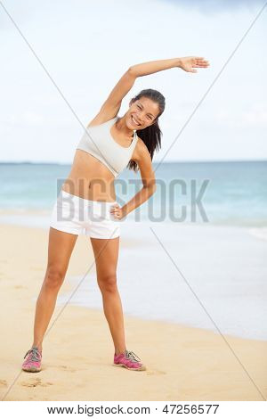 Fitness woman exercising training on beach stretching during exercise. Beautiful woman living healthy lifestyle working out outside. Happy smiling fit multiracial Asian Caucasian sport model.
