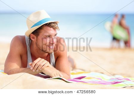 Man on beach lying in sand looking to side smiling happy wearing hipster summer hat. Young male model enjoying summer travel holiday by the ocean.