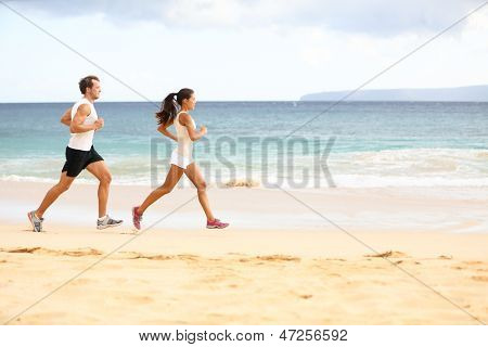Running people - woman and man athlete runners jogging in sand on beach. Fit young fitness couple exercising healthy lifestyle outdoors. Male athlete and female fitness model training together.