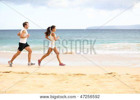 Ejecutando personas - hombre y mujer corredores atleta para correr en la arena en la playa. Fit fitness joven pareja ex