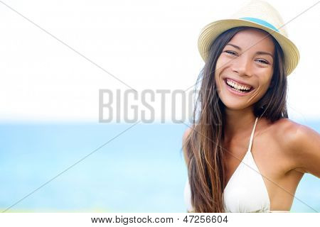 Woman - happy joyful beach summer girl portrait. Laughing lovely smiling multiracial young female model looking excited at camera wearing hipster hat by the ocean sea on sunny summer day by the water.