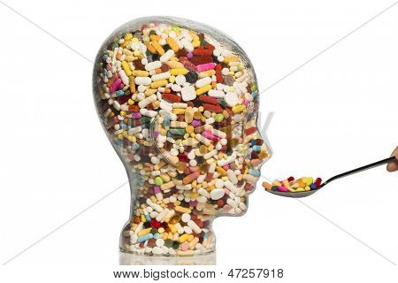a glass head filled with many tablets. photo icon for drugs, abuse and addiction tablets.