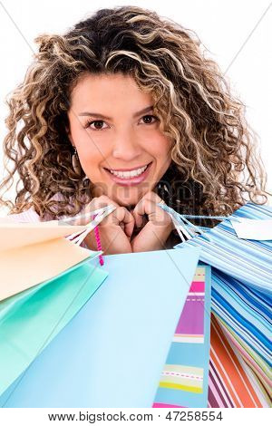 Happy female shopper holding shopping bags - isolated over white background