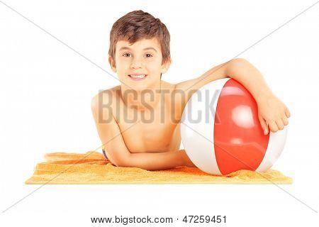 Glimlachend kind liggen op een strandhanddoek en houden een bal, geïsoleerd op witte achtergrond