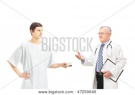 Male patient in hospital gown offering bribe to a medical doctor, isolated on white background