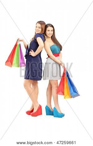Full length portrait of two friends holding shopping bags isolated on white background