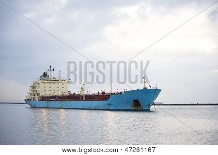 A blue shipping transportation freighter anchored just inside a port of call.