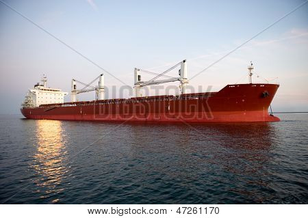A red shipping transportation freighter anchored just inside a port of call.