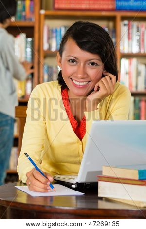 Student - Young woman in library with laptop learning, a male student standing in the Background on a shelf reading book