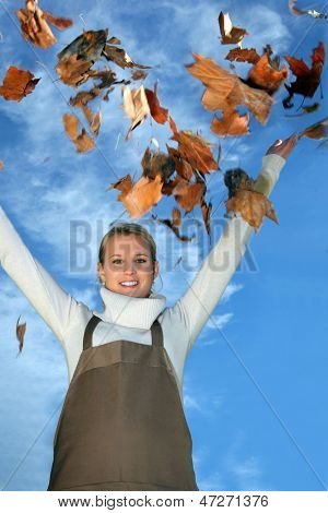 Young female gardener with autumn leaves