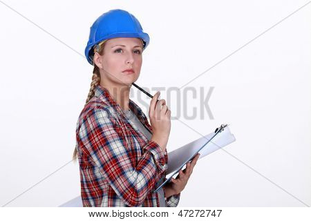 helmeted craftswoman with clipboard looking inspired