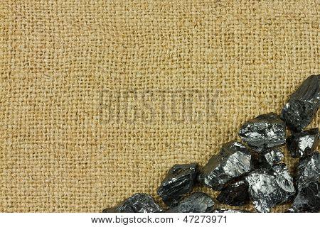 Raw Coal On Sack Background