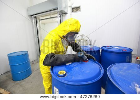Professional in uniform filling barrels with chemicals