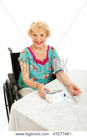 Beautiful senior woman in wheelchair taking her blood pressure with a home machine.  White background.