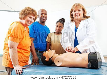 Adult students watching a nurse or doctor perform CPR on a mannequin.