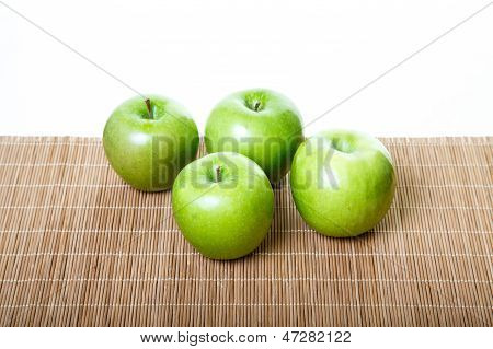 Four Green Apples On Bamboo Mat