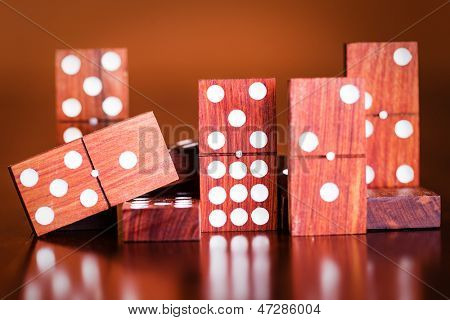 Tiles from a game of dominoes with reflections on a polished wooden table