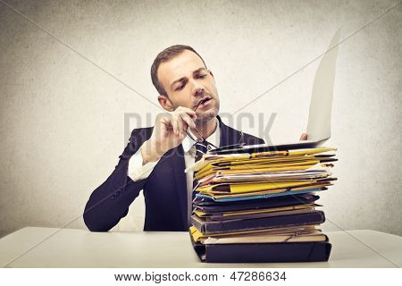 young businessman in the office with a lot of backlog